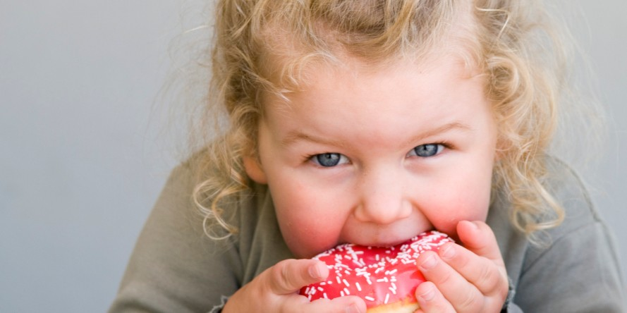 Little girl eating jelly-glazed donut with sprinkles